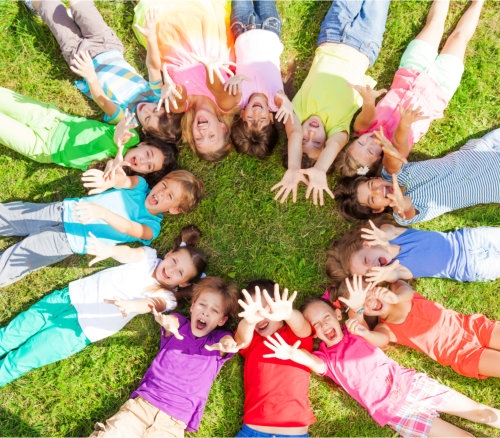 a circle of happy kids lying on the ground together